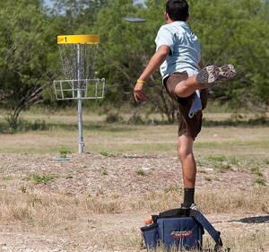 Photograph of someone putting at disc golf.